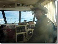 Conduciendo el yate con el sombrero oficial de capitán